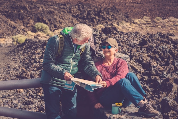 Couple adult senior man and woman trekker explorer during a rest over the mountains drinking a tea or coffee and looking at the paper map