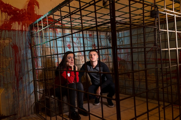 Couple of afraid halloween victims imprisoned in a metal cage with a blood splattered wall behind them sitting in terror