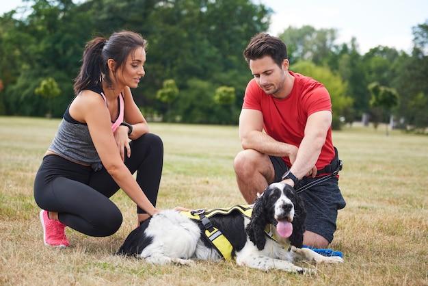 新鮮な空気でトレーニング後に休んでいるカップルと犬