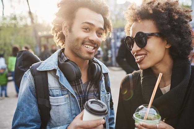 カップルと友情の概念。彼の妹と通りを歩いて、コーヒーを飲みながら話しているハンサムなアフリカ系アメリカ人の男