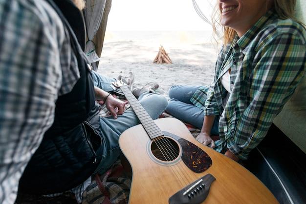 テントの中でカップルとギター