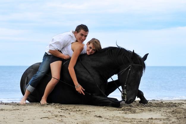 カップルとビーチの馬