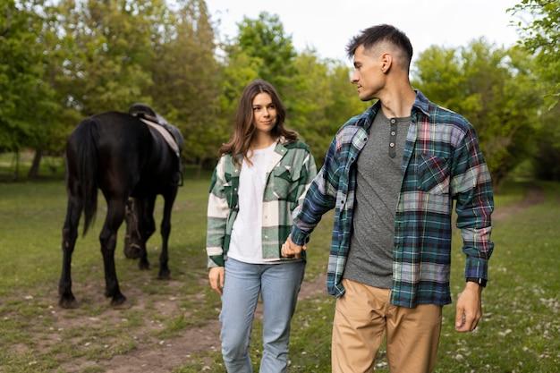 カップルと馬の屋外ミディアムショット