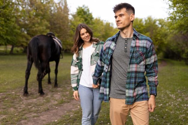 ミディアムショットの外のカップルと馬