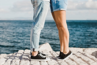 Couple and summer concept with legs in front of sea