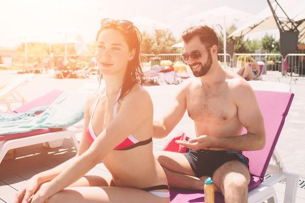 カップルが日焼け止めを適用します。ガールフレンドの背中にクリームを適用する幸せな若い男