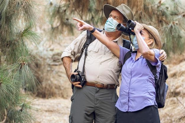 Coppia che apprezza la bellezza della natura con il binocolo durante la nuova normalità Foto Gratuite