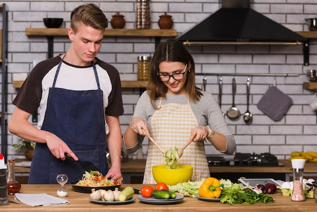 Couple in aprons cooking food in kitchen