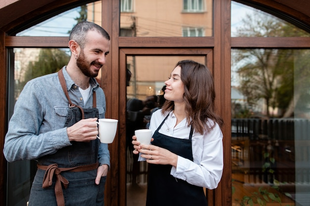 Couple in aprons enjoying coffee outside shop