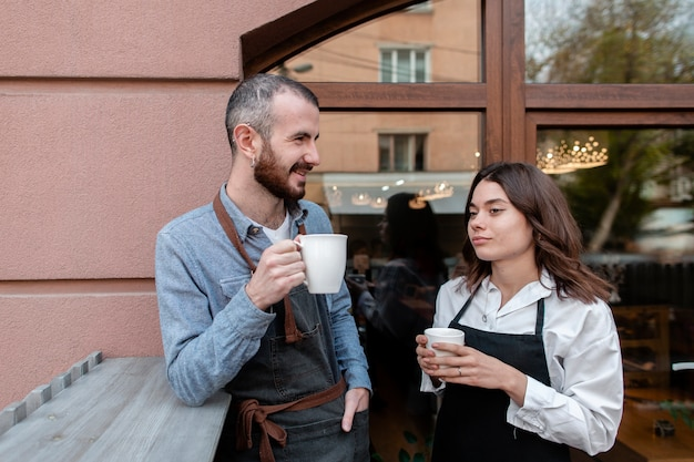 Couple in aprons enjoying coffee outside