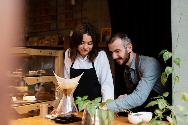 Couple in aprons looking at coffee filter