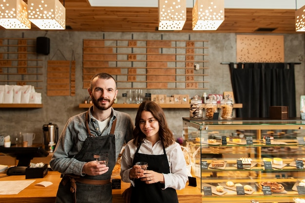 Couple in aprons posing with cups of coffee