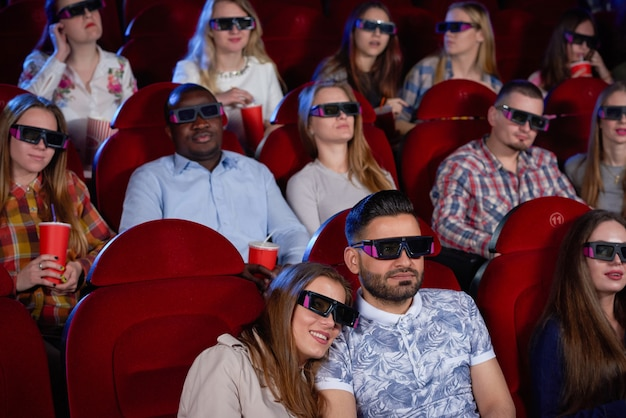 Пара арабских мужчина и брюнетка женщина сидят вместе в кино, обнимаются и смотрят комедию.