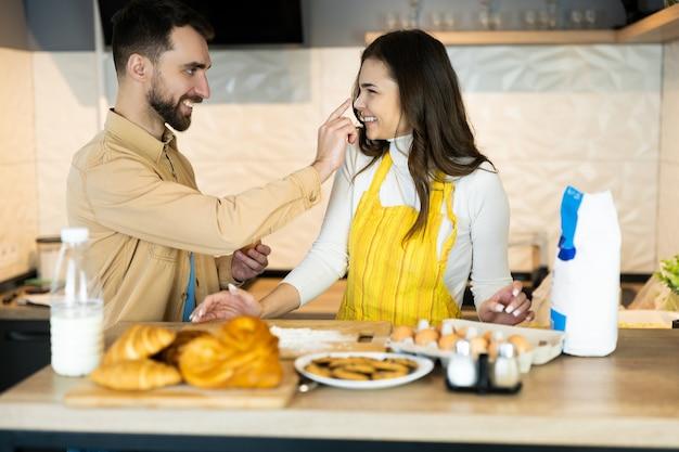 Пара развлекается во время приготовления пищи. кажется, они счастливы вместе на кухне.