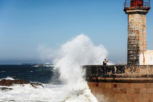 カップルは灯台の近くの海に立っています。