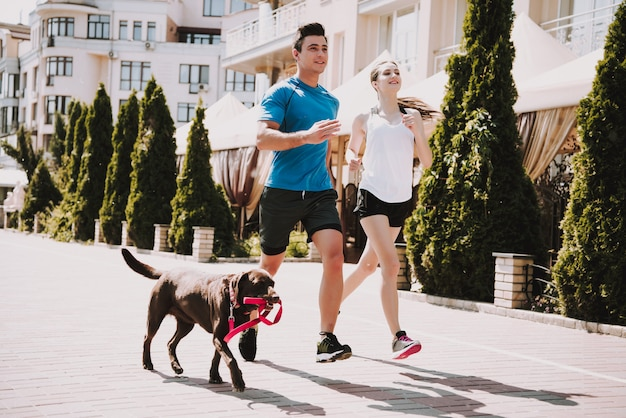 Couple are running on road with big dog