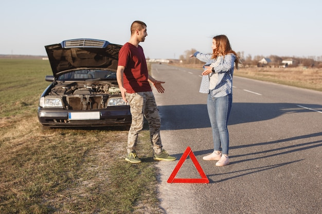 Couple argue on road, have problem with broken car, being in panic, don`t know what to do, red warning triangle warns other drivers about damage. husband and wife sort out relationship near auto
