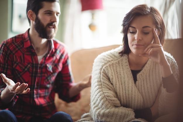 Пара спорят друг с другом в гостиной