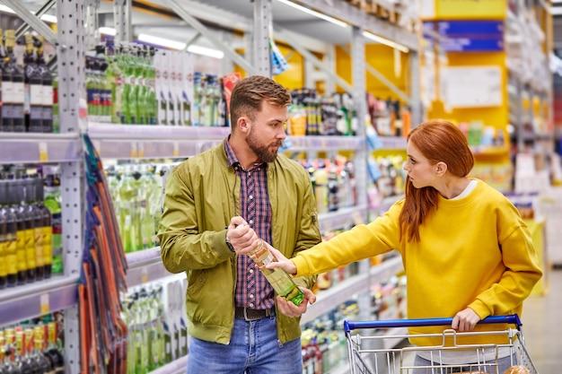 スーパーマーケットのアルコール部門で主張しているカップル、男性はアルコールを買いたい、女性は彼の選択に腹を立てている、不満