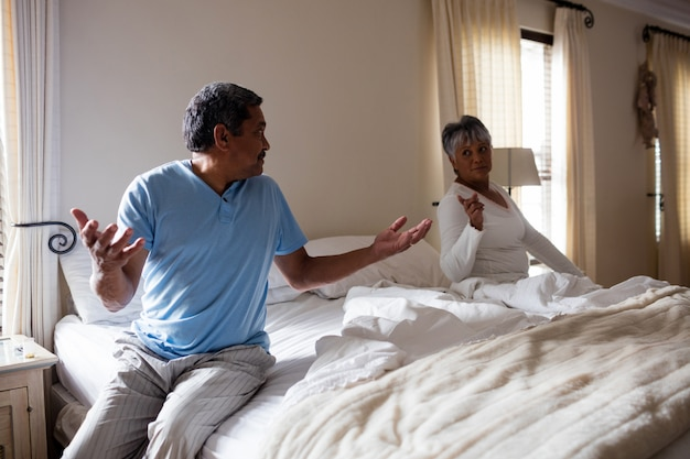 寝室でお互いと主張しているカップル