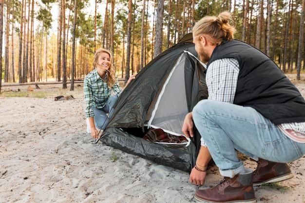 Пара, устанавливающая палатку на природе, вид сбоку