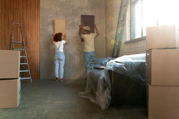 彼らの新しい家で絵をアレンジするカップル