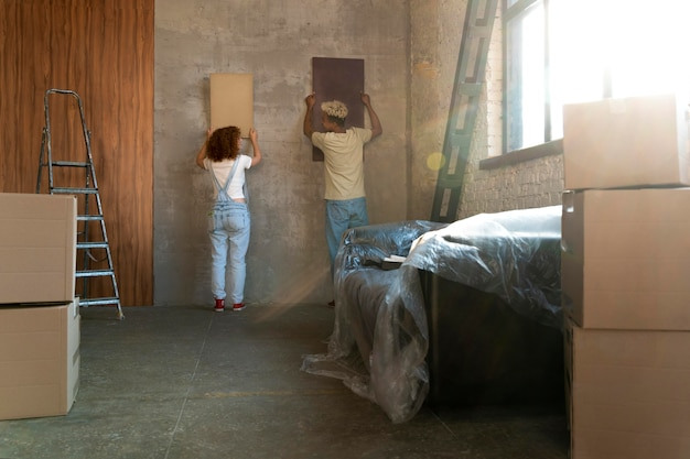 Couple arranging painting in their new home