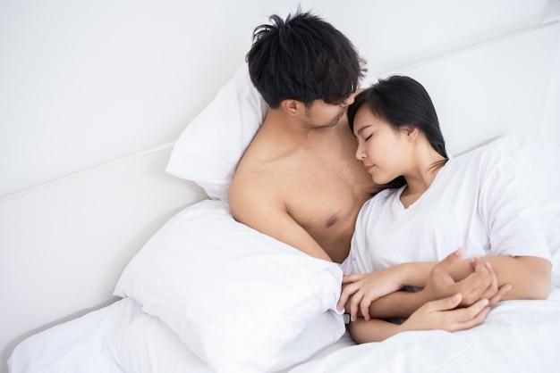 白い寝室のベッドでアジアの男性と女性のカップル