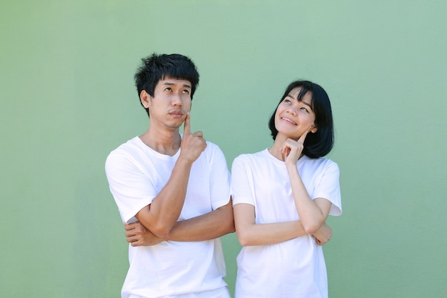 A couple of asian man woman pose thinking and looking top view