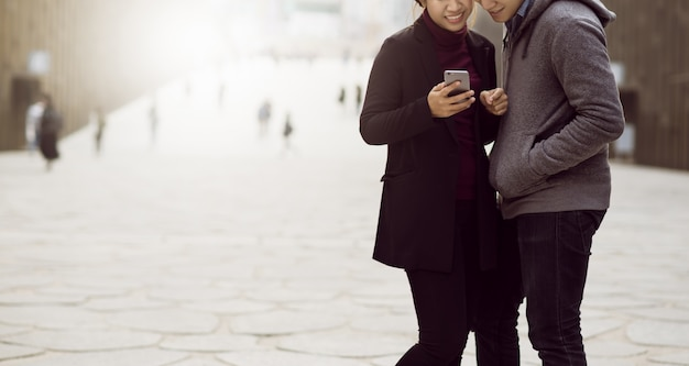 Couple asian using smartphone with city background.