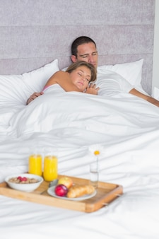 Couple asleep with breakfast tray on bed