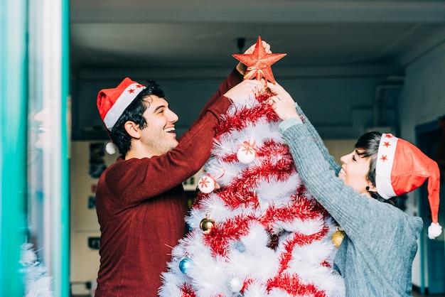 Couple assembling christmas tree