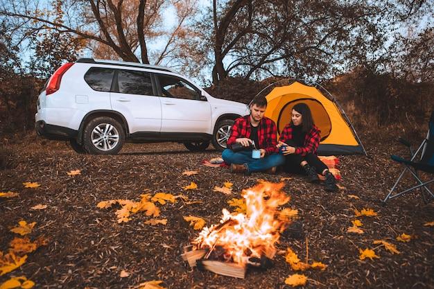 모닥불 텐트와 배경에 자동차 근처에 앉아 캠핑 사이트에서 커플