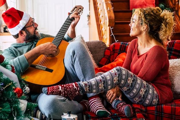 自宅でクリスマスを祝うカップルと笑顔と楽しみを一緒に楽しんでください-男性はギターを弾き、女性は彼を見ます。愛とレジャー屋内新年12月のライフスタイル