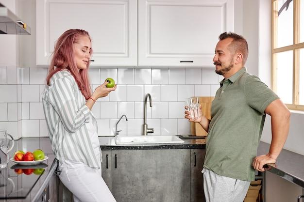 週末の自宅でのカップル、明るくモダンなキッチンでの美しいカップル、一緒に時間を過ごすことを楽しんで、話をする