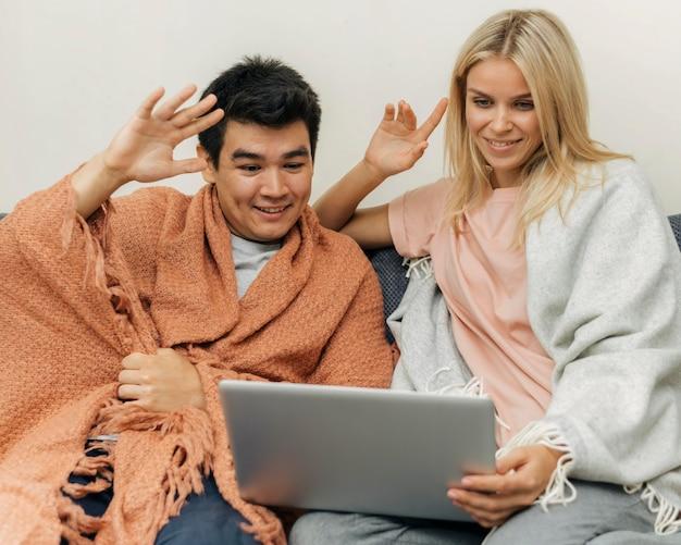 自宅でノートパソコンを使用して手を振っているカップル
