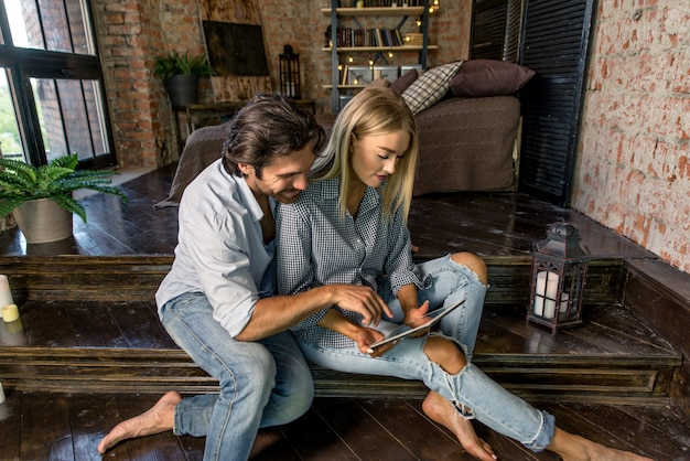 タブレットを見て自宅のカップル