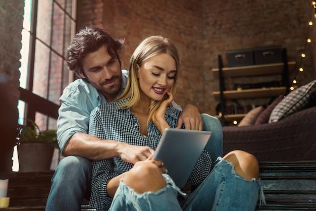 自宅でタブレットを見てカップル