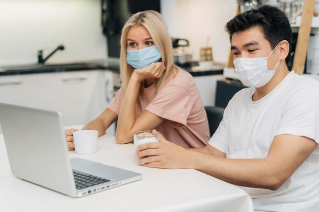 Пара дома с медицинскими масками во время пандемии работает на ноутбуке