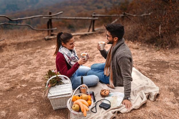 Пары на пикнике сидя на одеяле и выпивая чае в природе. осеннее время