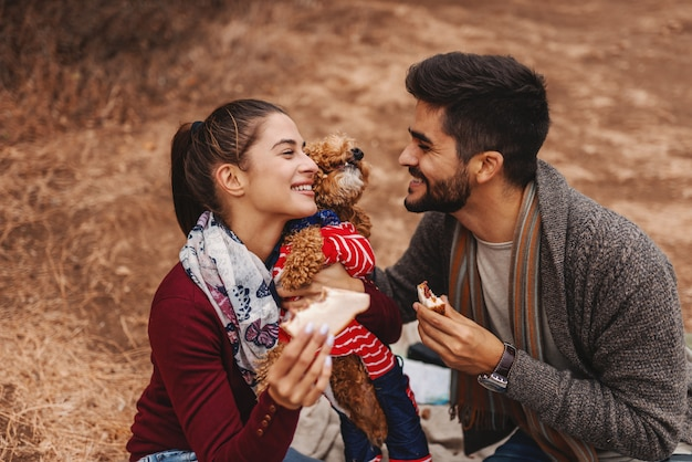 Пары на пикнике сидя на одеяле и играя с собакой. человек держа печенье пока женщина обнимая собаку. осеннее время