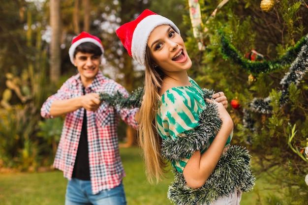クリスマスツリーでカップル。クリスマスの飾りで遊ぶ若いカップル。クリスマスを楽しんでいるカップル。クリスマスのコンセプト。