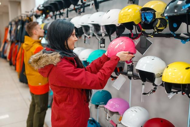 ショーケースでスキーやスノーボード用のヘルメットを選択するカップル