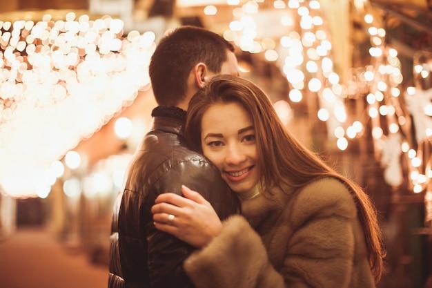 Пара на улице перед рождеством. боке огни украшения фон