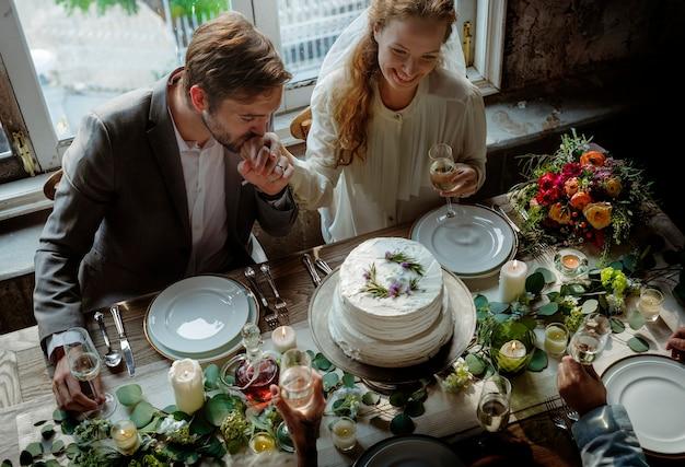 Пара за столом приема в день свадьбы
