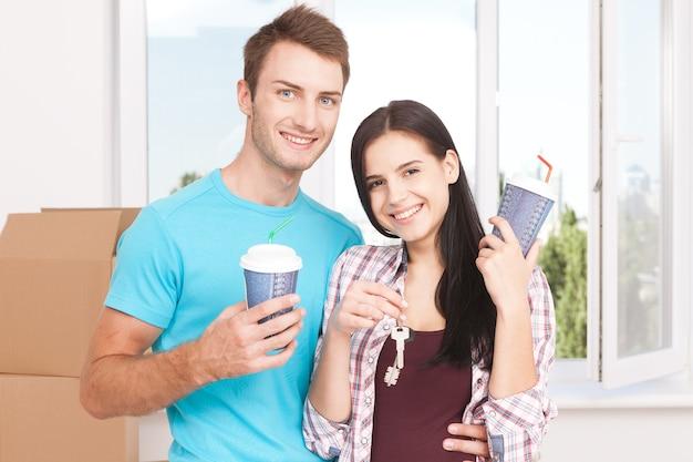 Пара в своей новой пустой квартире пьет кофе