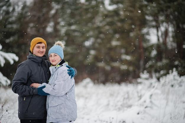 冬の日のカップル。雪と降雪のある寒い日に公園を散歩。