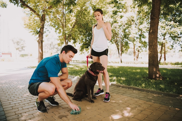 Couple of athletes with their dog in green park