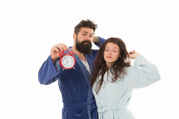 Пробуждение пары удерживает будильник. семейный утренний распорядок. создайте режим здорового отдыха, чтобы выспались. доброе утро. утреннее пробуждение. вредная привычка проспать. раннее утро. сонная женщина и мужчина.