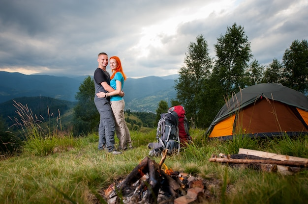 Couple backpackers standing near the campfire, tent, backpacks